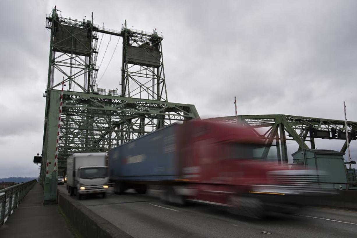 Trucks cross the Interstate 5 Bridge while traveling north on Tuesday morning. (Amanda Cowan/The Columbian)