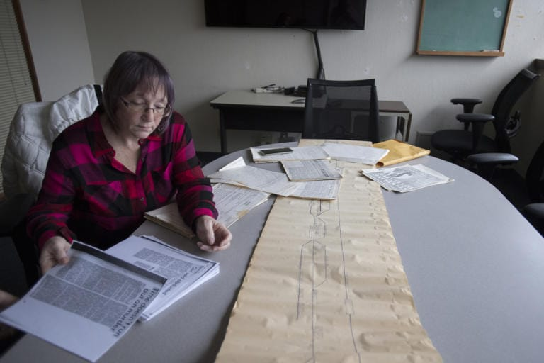 Norma Countryman looks over documents related to Warren Forrest's 1974 murder of Krista Blake at The Columbian on Jan. 10. On the table is a timeline used in the trial. (Amanda Cowan/The Columbian)
