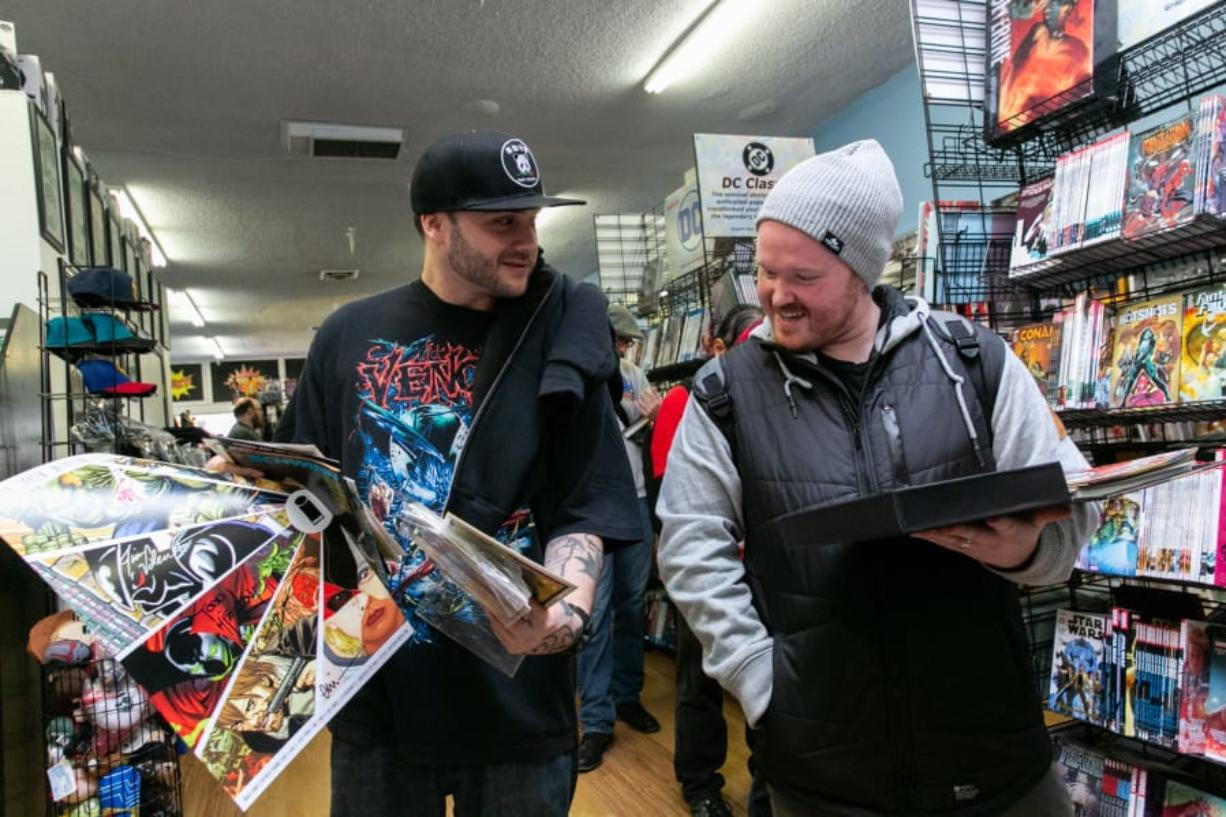 "Vancouver resident Bryan West, left, shows Nick Bishop of Vancouver his signed comic books at the Image Comics partner signing event at I Like Comics in Vancouver. The signing featured the creator of ""Spawn"" and ""The Walking Dead"" comic books, and drew more than 900 people."