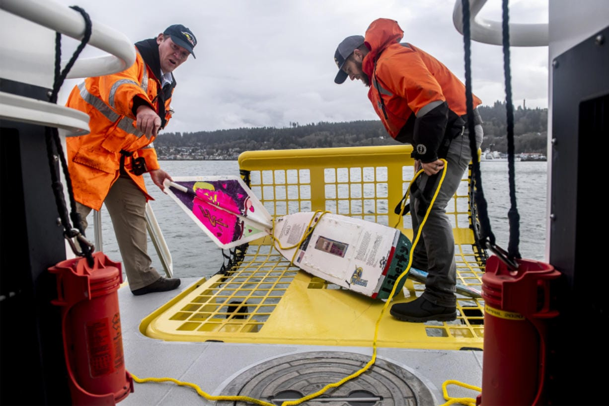 Bar pilot captain Dan Jordan, left, and deck hand Tyler Bartel pull the S/V Liberty miniboat from the Columbia River following a test launch in Astoria, Ore., on Tuesday afternoon.