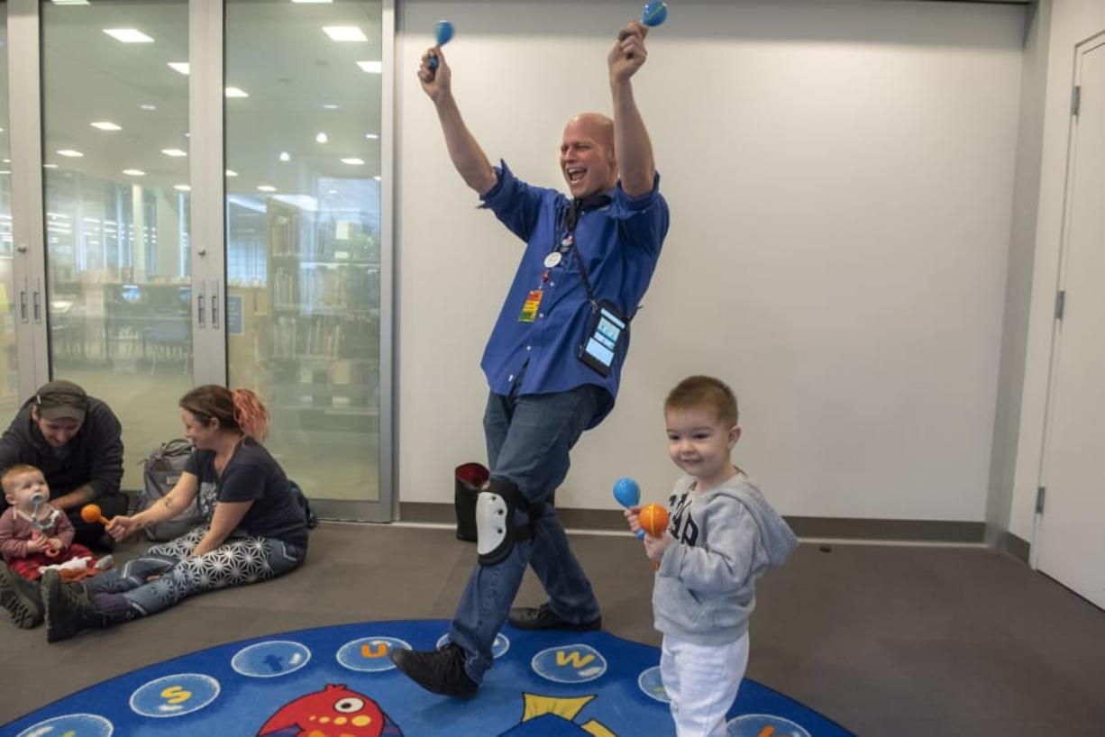 Senior Library Assistant Steve Williams, left, and Matteo Cojocaru, 2, lead the Baby Storytime group in song and dance at the Cascade Park Community Library on Thursday afternoon. The library soon will close for three weeks for minor remodeling.