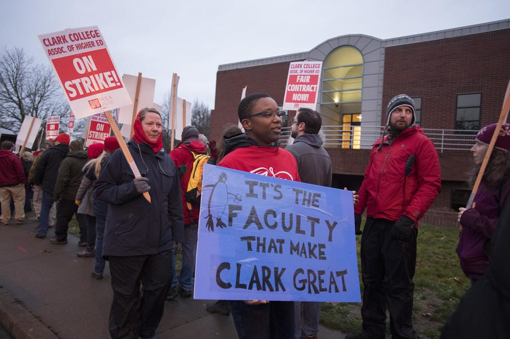 Christina Smith, who is an English professor, with blue sign, joins colleagues while striking at Clark College on Monday morning, Jan. 13, 2020. (Amanda Cowan/The Columbian)