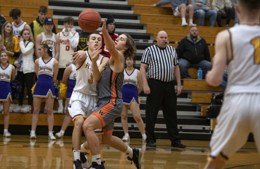 Washougalis Julien Jones (3) defends a pass from Columbia Riveris Alex Miller (3) at Columbia River High School on Friday night, Jan. 17, 2020.