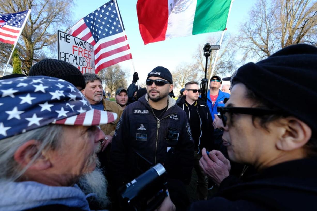 Patriot Prayer leader Joey Gibson, center, leads a protest in Portland in December 2017, a week after an undocumented Mexican resident of San Francisco was acquitted of the murder of Kate Seinle. It drew activists from both political extremes, including Kerry Hudson, left, who can be found at many Patriot Prayer rallies and Luis Enrique Marquez, right, a prominent anti-fascist protester. (Alex Milan Tracy/Portland Tribune)