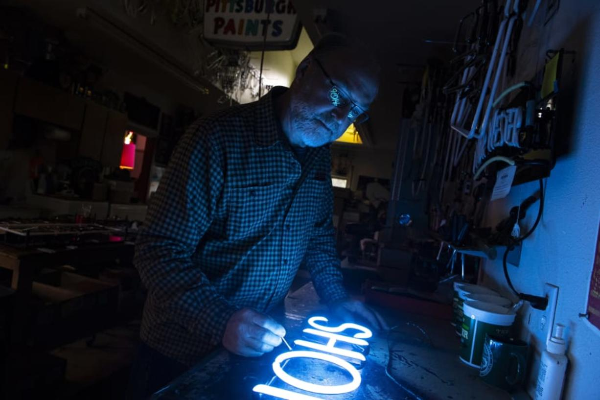 Roger Schurman, owner of Gas 'n Glass, applies touch-up paint to a barber shop's neon sign at his workshop in Ridgefield. (Photos by Nathan Howard/The Columbian)