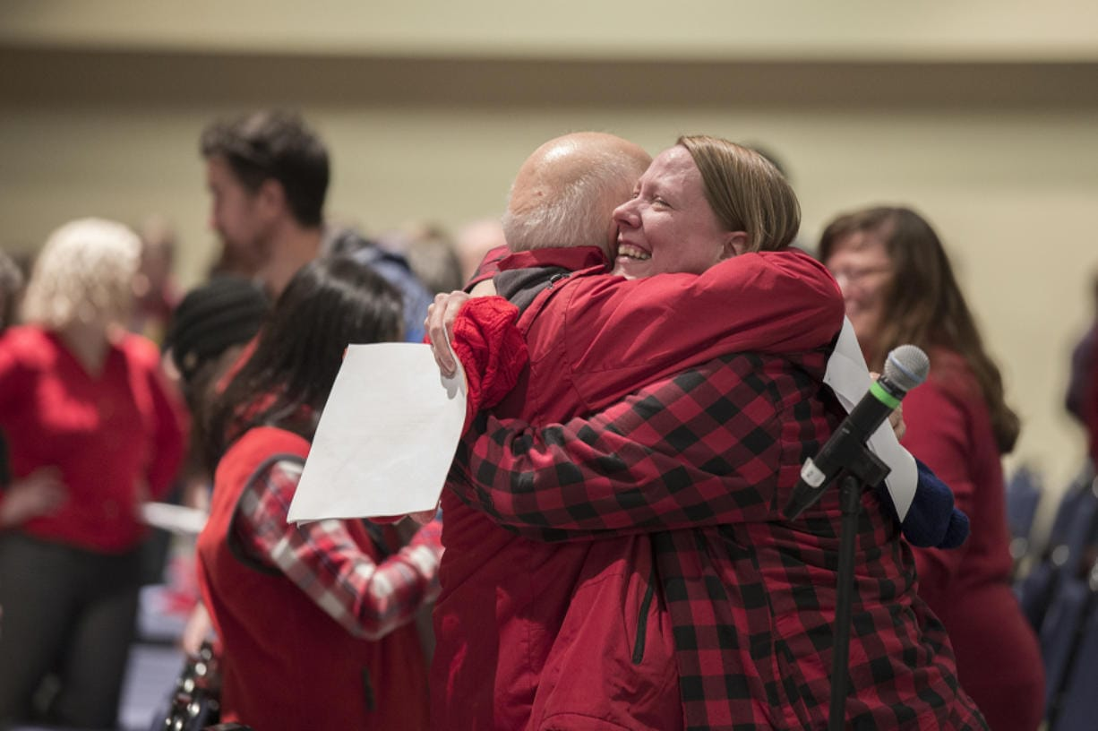 Clark College professor Michelle Roth, in plaid, hugs a colleague after the result of the union vote at Gaiser Hall on Wednesday. The union voted to ratify its new contract 257-9, drawing a three-day teacher strike to a close. (Amanda Cowan/The Columbian)