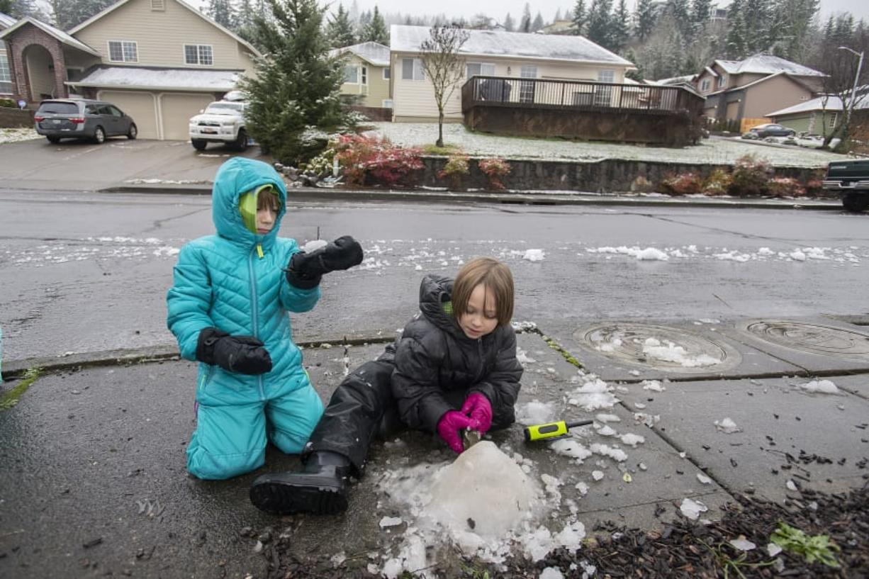 Finn Mullenberg, 6, left, of Washougal joins his sister, Lily, 8, as they try to make the most of the slushy, thawing snow near their home Thursday morning. The pair were among the students in Clark County who had the day off because of winter weather. (Amanda Cowan/The Columbian)