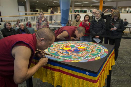 LEADOPTION Jampa Tenzin, left, and Ngawang Shakya, Tibetan Buddihist monks, attract a crowd while adding the finishing touches to a sand mandala at Clark College on Friday afternoon.  According to Tibetan Buddhist belief, a sand mandala is meant to create a profound experience of compassion for any who attend. (Amanda Cowan/The Columbian)