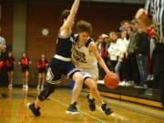 Union junior Kaden Horn dribbles around the defensive pressure from Skyview senior Sean Boss during Tuesday's 4A Greater St. Helens League matchup at Union High School. Horn scored 16 points in the Titans' victory.