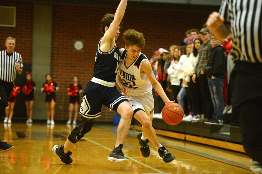Union junior Kaden Horn dribbles around the defensive pressure from Skyview senior Sean Boss during Tuesday's 4A Greater St. Helens League matchup at Union High School. Horn scored 16 points in the Titans' victory. (Samuel Wilson for The Columbian)