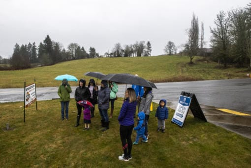 A group opposed to a proposed Verizon cell tower meets Thursday in front of the land where the tower would be built, across the street from Woodburn Elementary School. (Nathan Howard/The Columbian)