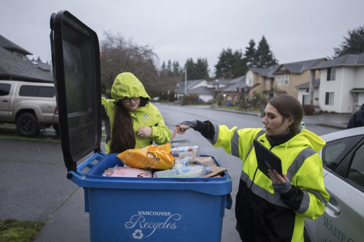 Gina Evans, left, and Jerin Dinkins, recycling specialists with Waste Connections of Washington, look for items that cannot be recycled Thursday morning in Vancouver's Burton-Evergreen neighborhood.