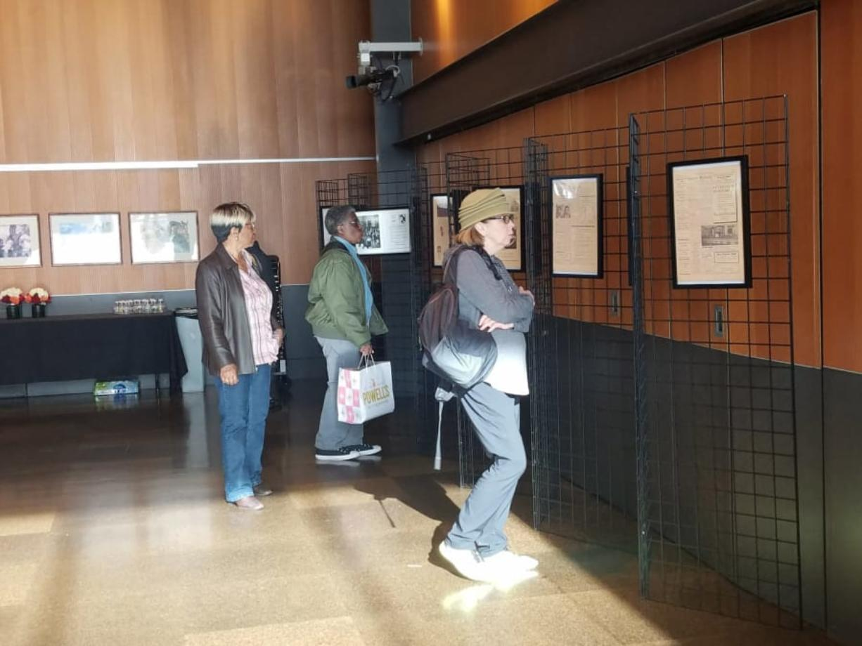 Attendees take in an exhibit honoring the history of African Americans in Clark County, part of an event to kick off a commemoration of Black History Month, on Saturday at the Vancouver Community Library.