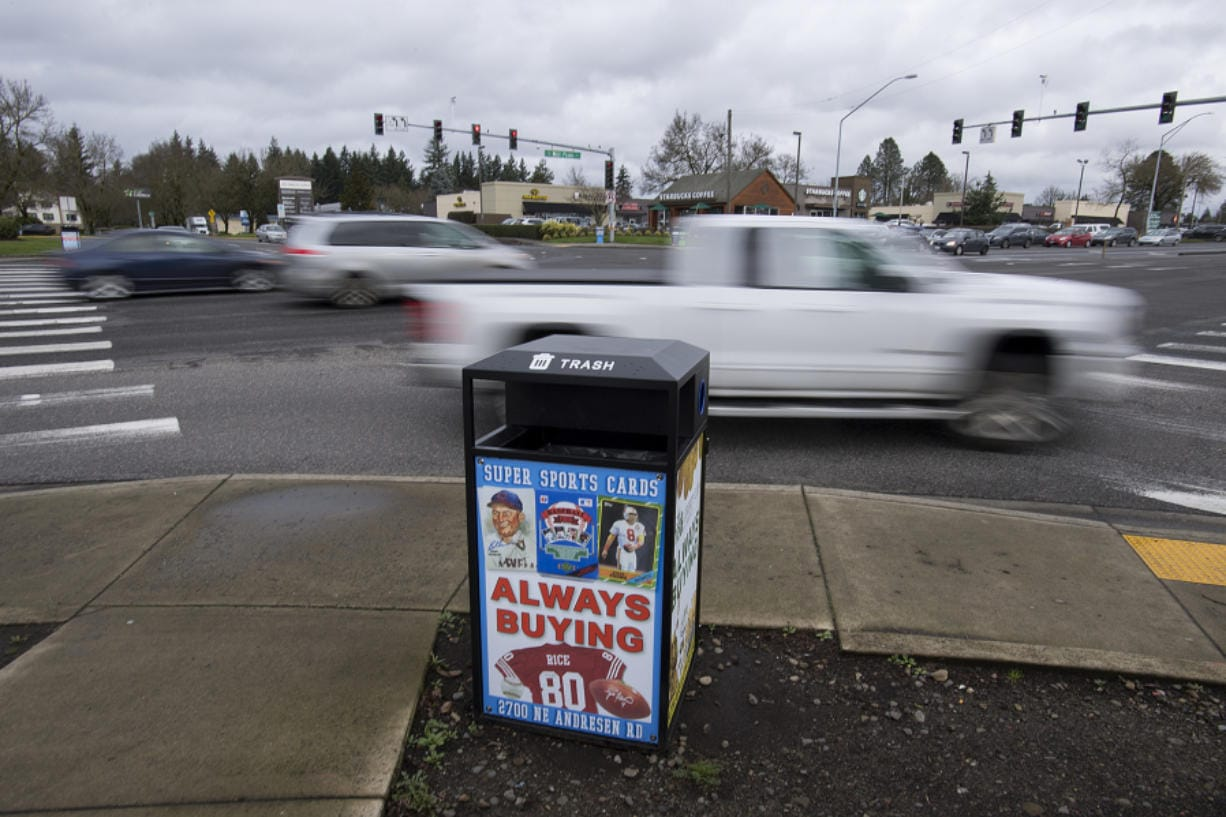 Motorists travel past a receptacle for garbage and recycling with advertisements at the corner of Southeast Chkalov Drive and Southeast Mill Plain Boulevard on Friday morning.
