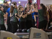 Members of the Evergreen High School girls bowling team celebrate after a shot during district bowling action at Crosley Lanes on Friday afternoon, Jan. 31, 2020.