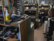Vitaliy Gerasimov, owner of Totem Shoe Repair, works on the stitching for a pair of sneakers.