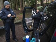 Tyler Chavers, Vancouver's Homeless Assistance Response Team officer, left, talks with Karalee Grunwald and her cat, Chyzeball, during the 2020 Point in Time count in Vancouver's Leverich Park. Grunwald said she's been homeless since June and was recently cited for unlawful camping.