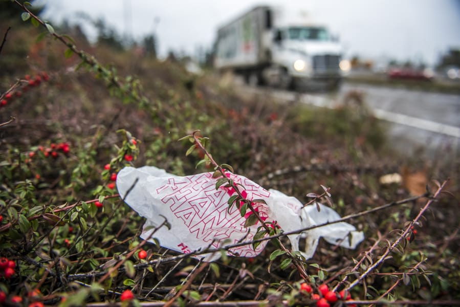 A plastic bag near passing traffic on Interstate 5 near downtown Vancouver. The Washington State Legislature is considering a bill that would ban single-use plastic bags at grocery store checkout lines and impose a fee on paper bags in order to encourage customers to switch to re-usable bags.