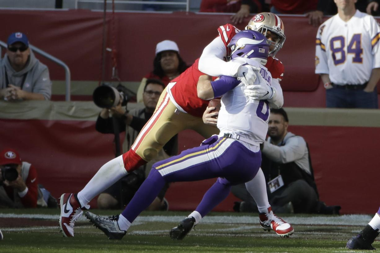 Minnesota Vikings quarterback Kirk Cousins, right, is sacked by San Francisco 49ers defensive end Arik Armstead during the first half of an NFL divisional playoff football game, Saturday, Jan. 11, 2020, in Santa Clara, Calif. (AP Photo/Marcio Jose Sanchez)