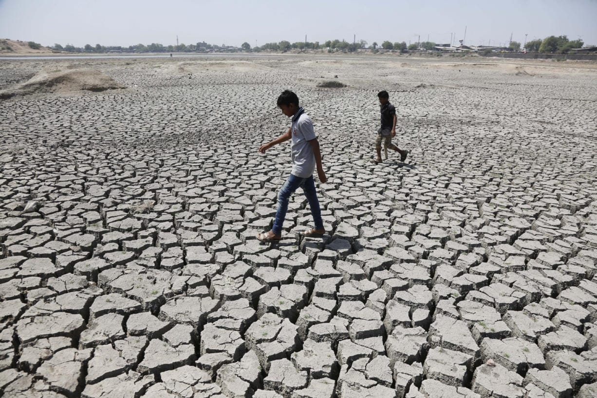 FILE - In this May 14, 2016, file photo, boys on their way to play cricket walk through a dried patch of Chandola Lake in Ahmadabad, India. The decade that just ended was by far the hottest ever measured on Earth, capped off by the second-warmest year on record, NASA and the National Oceanic and Atmospheric Administration reported Wednesday, Jan. 15, 2020.