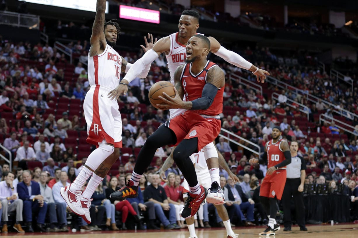 Portland Trail Blazers guard Damian Lillard, middle, puts up a shot in front of Houston Rockets guard Ben McLemore (16) and guard Russell Westbrook, back, as forward Carmelo Anthony (00) looks on during the first half of an NBA basketball game Wednesday, Jan. 15, 2020, in Houston.