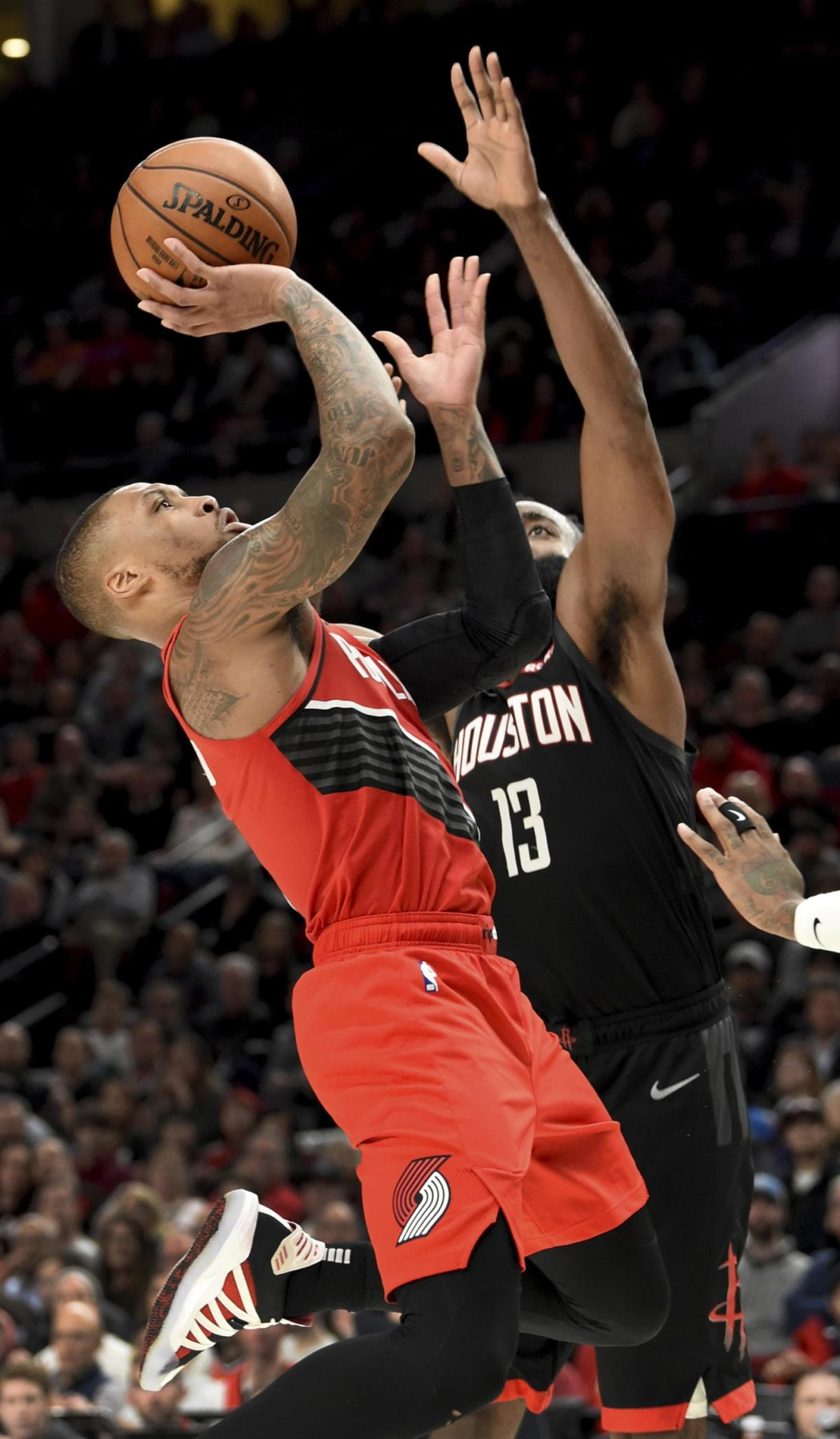 Portland Trail Blazers guard Damian Lillard, left, drives to the basket as Houston Rockets guard James Harden defends during the second half of an NBA basketball game in Portland, Ore., Wednesday, Jan. 29, 2020. The Blazers won 125-112. (AP Photo/Steve Dykes)