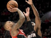 Portland Trail Blazers guard Damian Lillard, left, drives to the basket as Houston Rockets guard James Harden defends during the second half of an NBA basketball game in Portland, Ore., Wednesday, Jan. 29, 2020. The Blazers won 125-112.