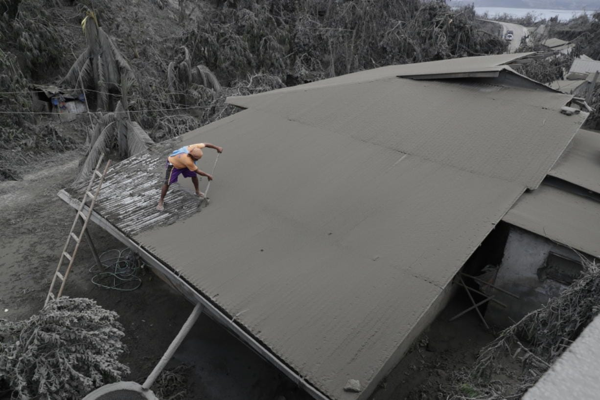 A resident clears volcanic ash from his roof Tuesday in Laurel, Philippines.
