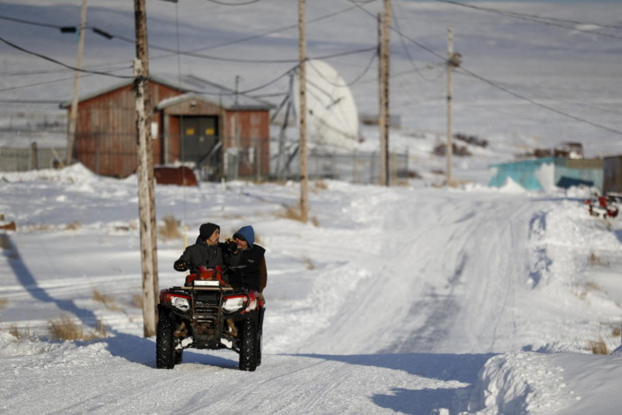 People ride through town on all-terrain vehicles Saturday, Jan. 18, 2020, in Toksook Bay, Alaska. The first Americans to be counted in the 2020 Census starting Tuesday, Jan. 21, live in this Bering Sea coastal village. The Census traditionally begins earlier in Alaska than the rest of the nation because frozen ground allows easier access for Census workers, and rural Alaska will scatter with the spring thaw to traditional hunting and fishing grounds.