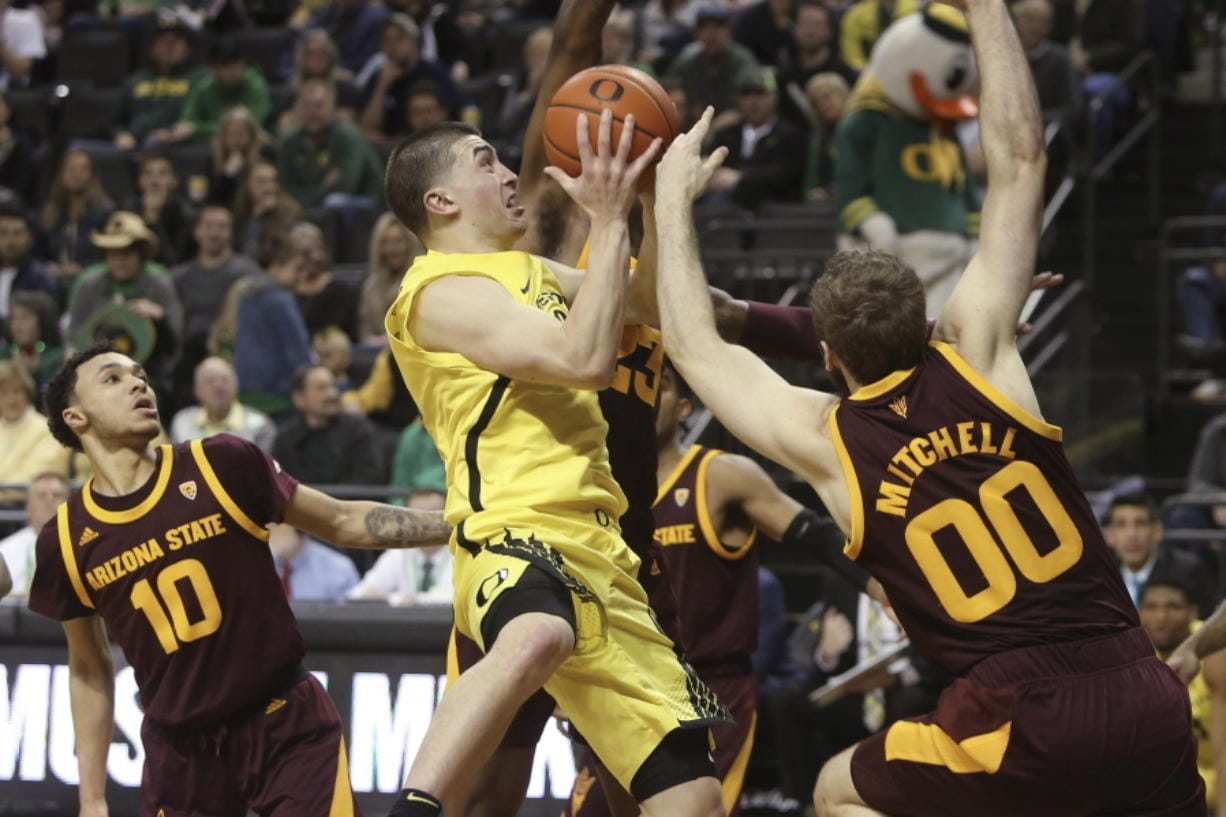 Oregon's Payton Pritchard, center, is fouled while going to the basket between Arizona State's Jaelen House, left, and Mickey Mitchell, right, during the second half of an NCAA college basketball game in Eugene, Ore., Saturday, Jan. 11, 2020.