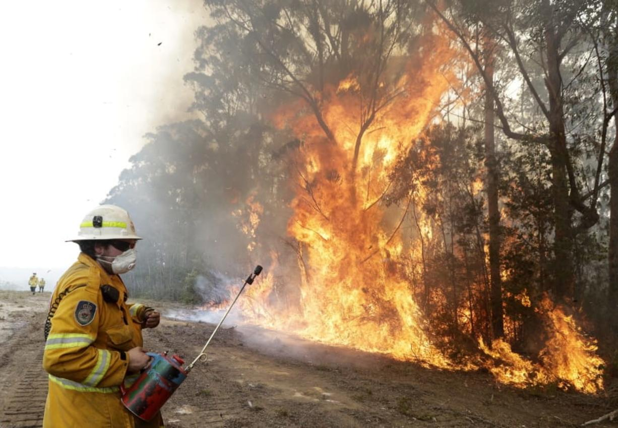 A firefighters backs away from the flames Wednesday after lighting a controlled burn near Tomerong, Australia, in an effort to contain a larger fire nearby. (Rick Rycroft/Associated Press)