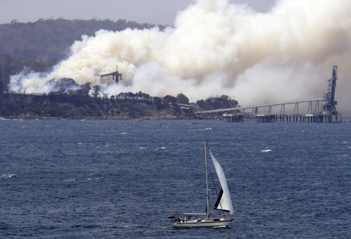 A yacht sails past a burning woodchip mill as the wildfires hits the town of Eden, New South Wales, Australia, Friday, Jan. 10, 2020. The wildfires have destroyed more than 2,000 homes and continue to burn, threatening to flare up again as temperatures rise.