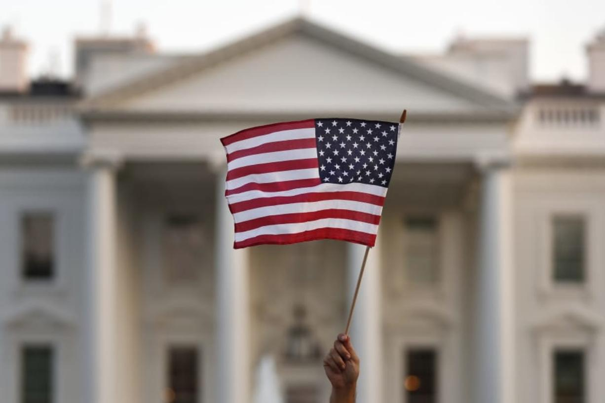 FILE - In this Sept. 2017 file photo, a flag is waved during an immigration rally outside the White House, in Washington. President Donald Trump has touted the creation of an office created to help victims of crimes committed by people in the U.S. illegally. But most of the people calling the Trump administration hotline aren't calling to get information. They are calling to report their neighbors, colleagues or strangers who they suspect are in the country illegally.