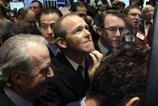 Then-Nielsen Company CEO David Calhoun, center, watches progress as he waits for the company's IPO to begin trading, on the floor of the New York Stock Exchange. Calhoun, Boeing's new CEO, said Wednesday that production of the 737 Max will resume this spring, months before the company expects federal regulators to certify the grounded plane to fly again. (AP Photo/Richard Drew, File)