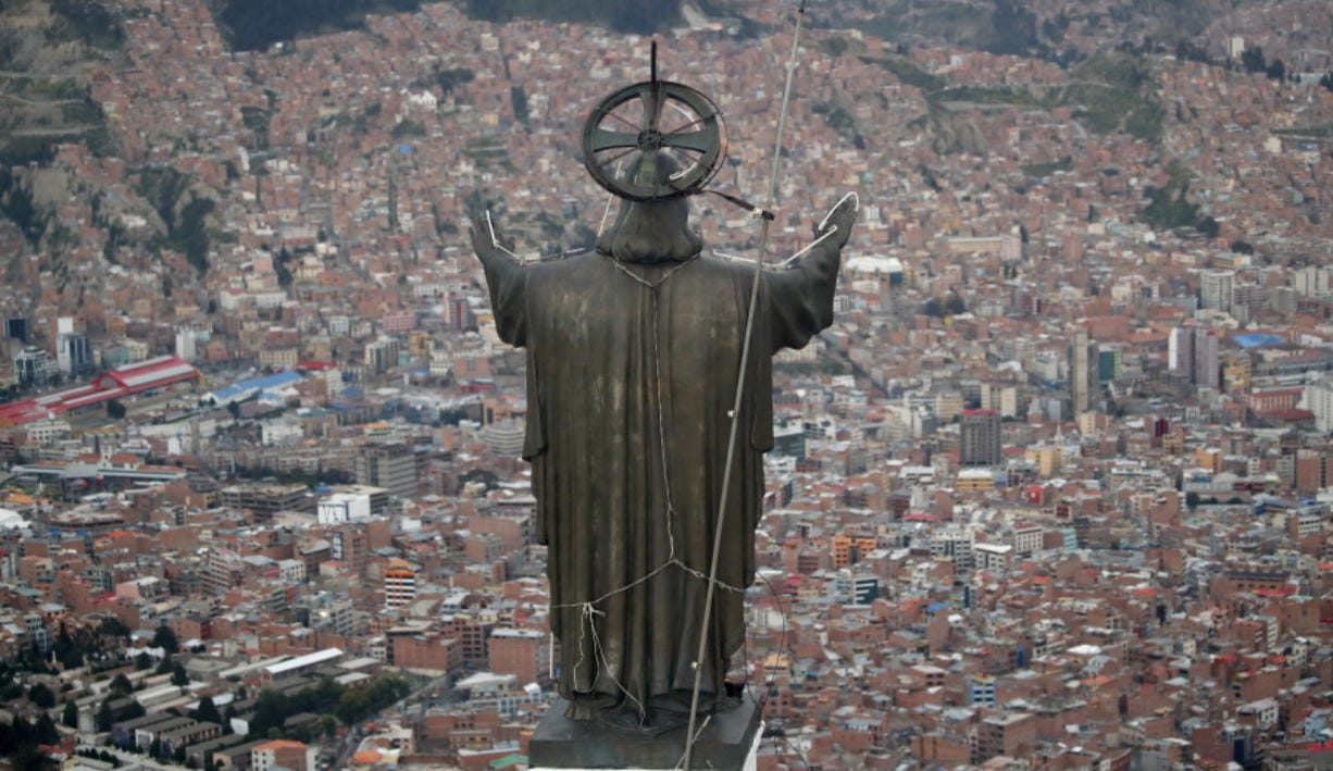 A Christ statue overlooks El Alto, a city adjoining the capital city La Paz, Bolivia. Ancestral indigenous practices became more visible during the presidency of Evo Morales, who recognized the Andean earth deity Pachamama.