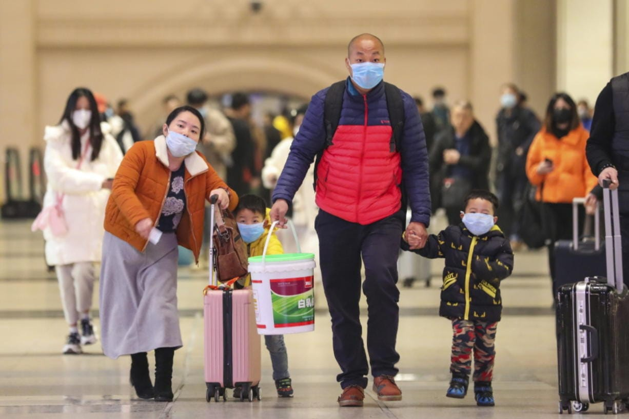 In this photo taken Tuesday, Jan. 21, 2020, travelers wearing face masks walk with their luggage at Hankou Railway Station in Wuhan in southern China's Hubei province. The U.S. on Tuesday reported its first case of a new and potentially deadly virus circulating in China, saying a Washington state resident who returned last week from the outbreak's epicenter was hospitalized near Seattle. (Chinatopix via AP)