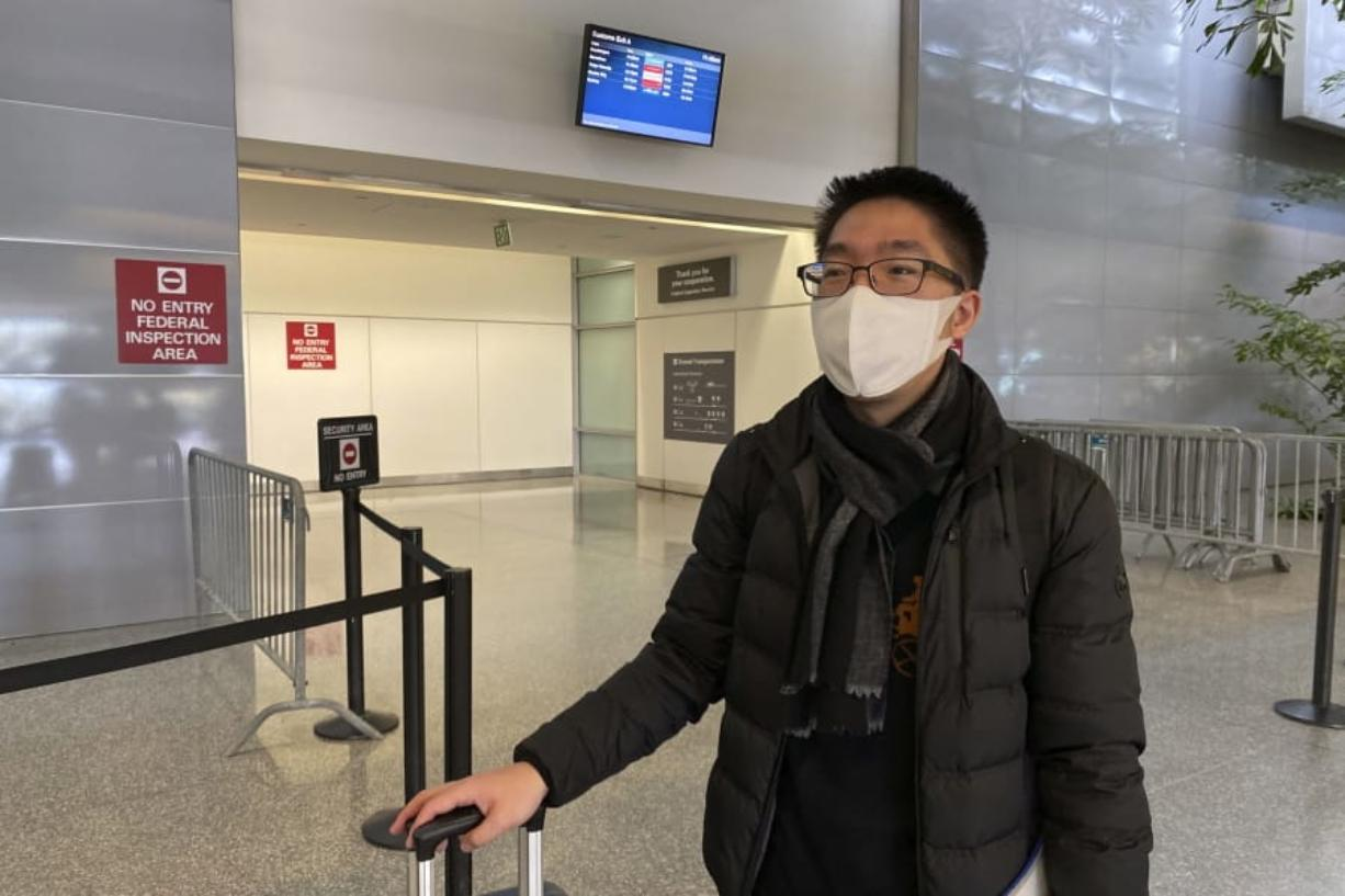 "In this Wednesday, Jan. 29, 2020, photo, Bill Chen stands outside of customs at San Francisco International Airport after arriving on a flight from Shanghai, where he was conducting business and visiting family over the Lunar New Year holiday. Chen said his temperature was quickly screened at the Shanghai airport before he departed. He also filled out a health questionnaire that asked if he had traveled to Wuhan or had any contact with someone who had been in the city, the epicenter of the coronavirus. ""I feel a little bit sorry for people traveling on the plane,"" Chen said. ""People have to be nervous in some way."" (AP Photo/Terry Chea)"