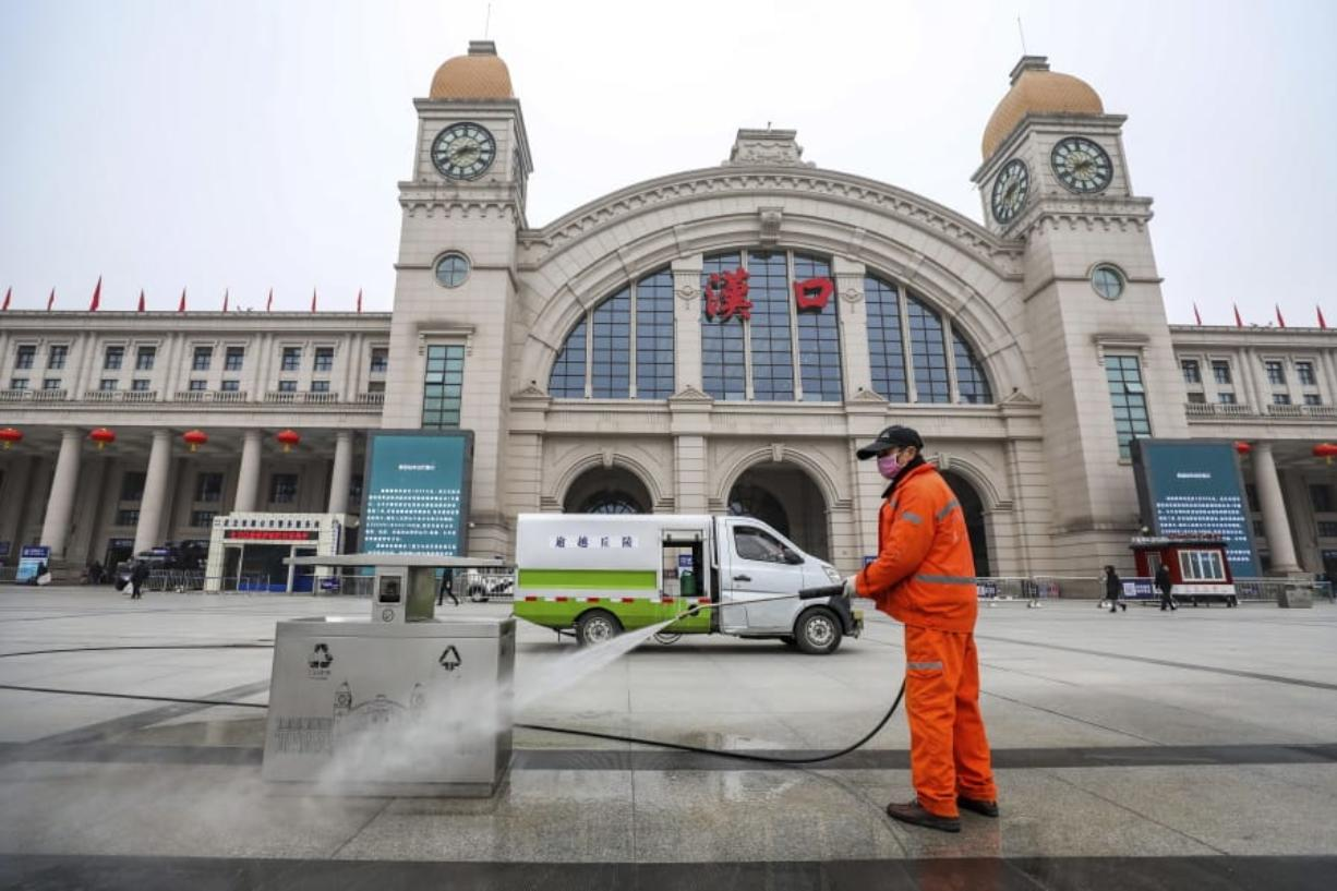 A worker hoses down garbage bins outside the closed Hankou Railway Station in Wuhan in central China's Hubei Province, Thursday, Jan. 23, 2020. Overnight, Wuhan authorities announced that the airport and train stations would be closed, and all public transportation suspended by 10 a.m. Friday. Unless they had a special reason, the government said, residents should not leave Wuhan, the sprawling central Chinese city of 11 million that's the epicenter of an epidemic that has infected nearly 600 people. (Chinatopix via AP)