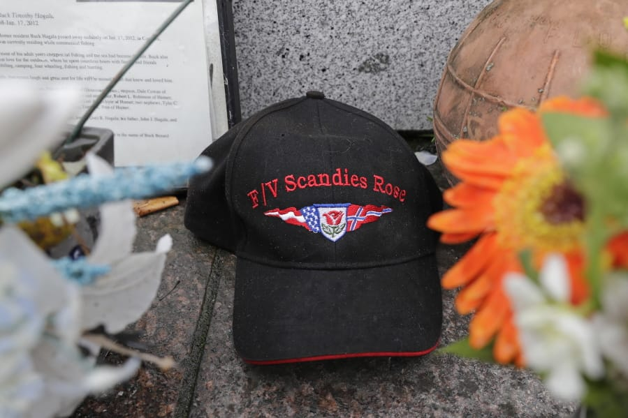 A ball cap with the name of the crab fishing boat Scandies Rose rests at the Seattle Fishermen's Memorial, Thursday, Jan. 2, 2020, in Seattle. The search for five crew members of the Scandies Rose in Alaska has been suspended, the U.S. Coast Guard said after two other crew members of the vessel were rescued after the 130-foot crab fishing boat from Dutch Harbor, Alaska, sank on New Year's Eve. (AP Photo/Ted S.