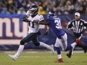 Philadelphia Eagles quarterback Carson Wentz (11) runs with the ball past New York Giants defensive back Michael Thomas (31) in the first half of an NFL football game, Sunday, Dec. 29, 2019, in East Rutherford, N.J.