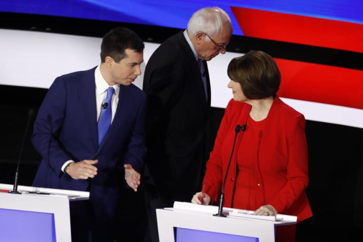 Democratic presidential candidates former South Bend Mayor Pete Buttigieg, left, and Sen. Amy Klobuchar, D-Minn., talk while Sen. Bernie Sanders, I-Vt., heads off stage at a break Tuesday, Jan. 14, 2020, during a Democratic presidential primary debate hosted by CNN and the Des Moines Register in Des Moines, Iowa.