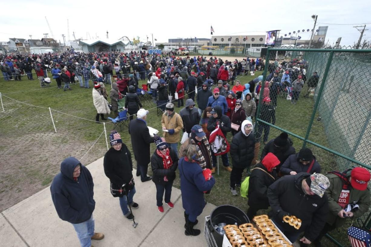 People stand in the cold in a field, as they line up to enter the Wildwoods Convention Center for a campaign rally with President Donald Trump, Tuesday, Jan. 28, 2020, in Wildwood, N.J.
