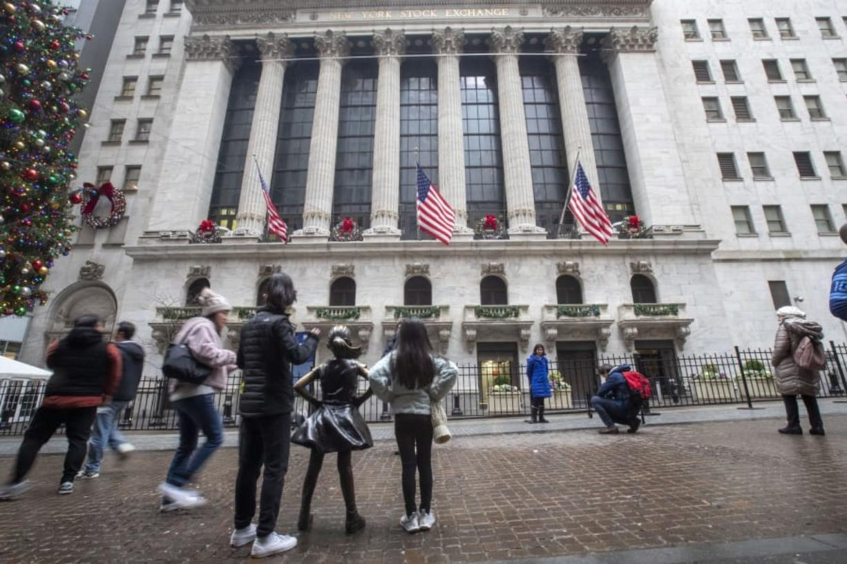 FILE - In this Jan. 3, 2020, file photo visitors to the New York Stock Exchange pause to take photos in New York. The U.S. stock market opens at 9:30 a.m. EST on Wednesday, Jan. 8.