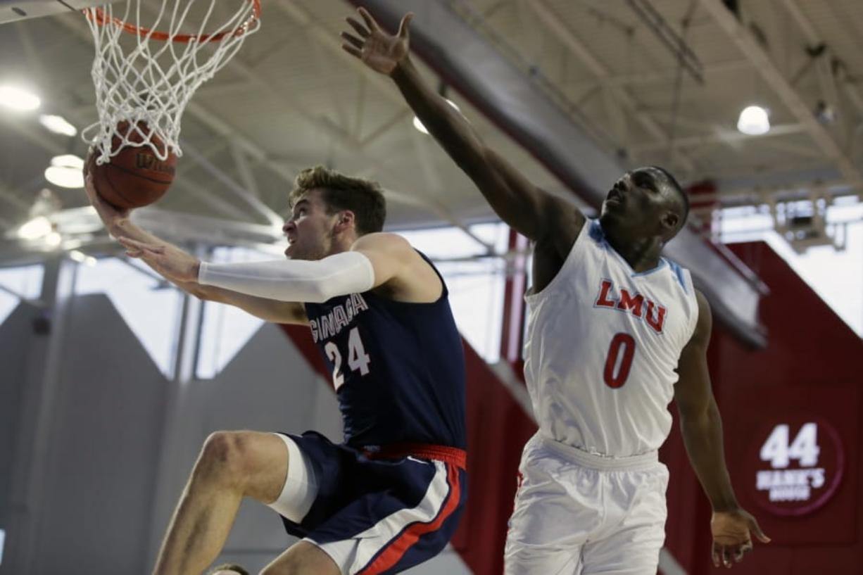 Gonzaga forward Corey Kispert, left, drives past Loyola Marymount guard Eli Scott, right, during the first half of an NCAA college basketball game in Los Angeles, Saturday, Jan. 11, 2020.
