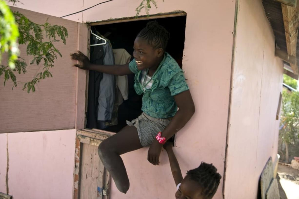 In this Jan. 3, 2020 photo, Rose-Berline Thomas sits in a window to speak with her mother outside at their home in Canaan, a district in Croix des Bouquets, Haiti, created for people who lost their homes in the earthquake 10 years ago. Rose-Berline Thomas was 2-years-old when the earthquake collapsed her family's home on top of her, crushing her foot.