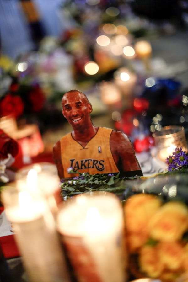 A picture of the late Kobe Bryant is displayed at a memorial near Staples Center, Tuesday, Jan. 28, 2020, in Los Angeles. Bryant, the 18-time NBA All-Star who won five championships and became one of the greatest basketball players of his generation during a 20-year career with the Los Angeles Lakers, died in a helicopter crash Sunday. (AP Photo/Ringo H.W. Chiu)