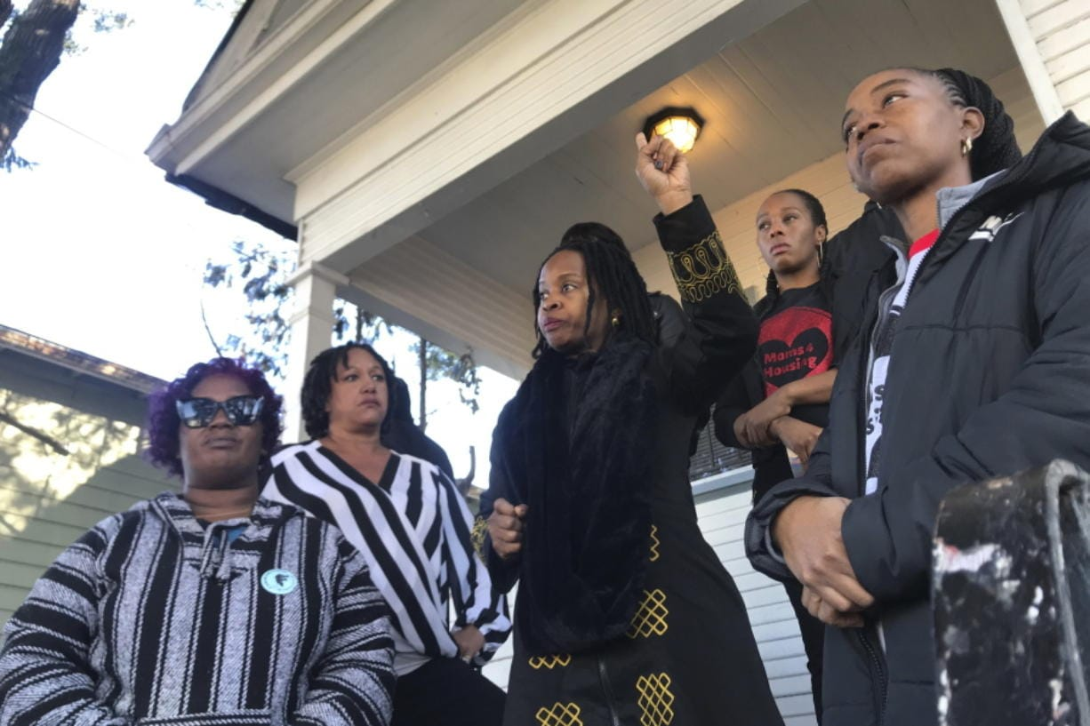 FILE - In this Dec. 30, 2019, file photo, Sharena Thomas, left, Carroll Fife, center, Dominique Walker, second from right, and Tolani KIng, right, stand outside a vacant home they took over on Magnolia Street in West Oakland, Calif. Homeless women ordered by a judge last week to leave a vacant house they occupied illegally in Oakland for two months have been evicted by sheriff's deputies. They removed two women and a male supporter Tuesday, Jan. 14, 2020, from the home before dawn in a case highlighting California's severe housing shortage and growing homeless population.