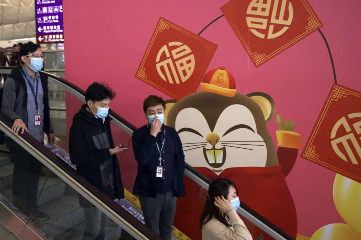 People wear face masks as they ride an escalator at the Hong Kong International Airport in Hong Kong, Tuesday, Jan. 21, 2020. Face masks sold out and temperature checks at airports and train stations became the new norm as China strove Tuesday to control the outbreak of a new coronavirus that has reached four other countries and territories and threatens to spread further during the Lunar New Year travel rush. (AP Photo/Ng Han Guan) (Port of Seattle)