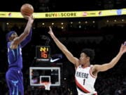 Charlotte Hornets guard Devonte' Graham, left, shoots the ball over Portland Trail Blazers guard Anfernee Simons, right, during the first half of an NBA basketball game in Portland, Ore., Monday, Jan. 13, 2020.
