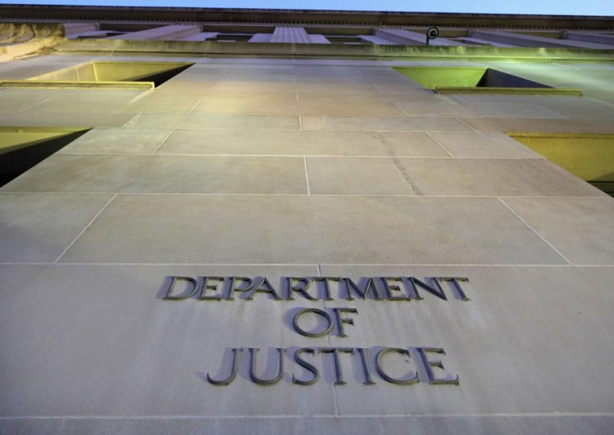 FILE - In this May 14, 2013, file photo, the Department of Justice headquarters building in Washington is photographed early in the morning. The Executive Office for Immigration Review is the arm of the Justice Department that oversees deportation proceedings -- whether immigrants are allowed stay in the U.S. or whether they are turned back to their countries. (AP Photo/J. David Ake, File)
